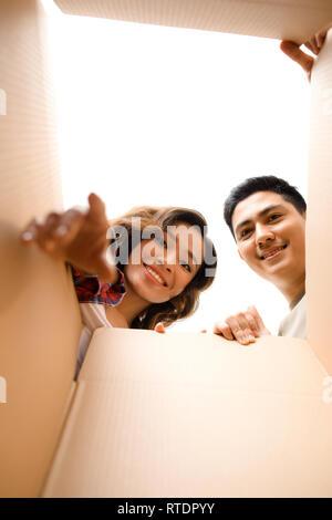 Smiling young couple ouverture d'une boîte en carton et à l'intérieur, de la réinstallation et le déballage concept Banque D'Images