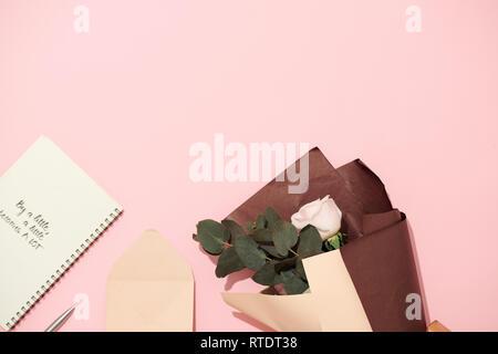 Ordinateur portable ouvert avec des pages blanches sur fond rose avec magnifique bouquet de roses Banque D'Images