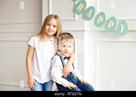 Cute boy dans une chemise blanche est assise sur une chaise dans une salle lumineuse soeur épouse ses épaules Banque D'Images