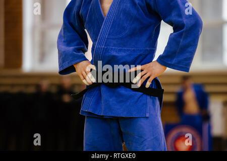 Un athlète de judo en kimono bleu et noir belt