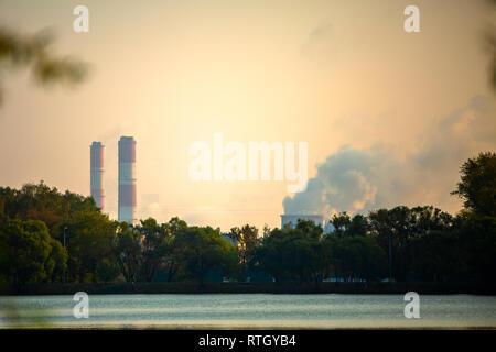 Photo d'arbres, rivière, des tuyaux de fumée. Banque D'Images