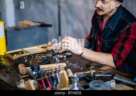 Bijoutier laborieux travail avec différents morceaux de métal, Close up side view photo. travail, profession Banque D'Images