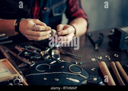 Man's hands shapingthe pièces de métal. close up photo recadrée Banque D'Images