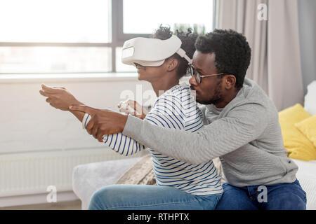 Beau couple à l'aide de dispositifs électroniques de technologie futuriste. Femme africaine jouant jeu d'ordinateur à couper le souffle avec casque VR et son mari il Banque D'Images