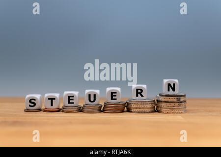 """Formulaire dés le mot allemand """"TEUERN"""" (""""taxe"""" en anglais) sur le dessus des piles de pièces. Concept d'augmentation des impôts. Banque D'Images"""