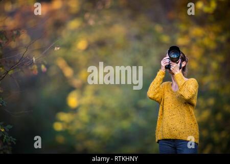 Jolie femme photographe à prendre des photos en plein air, sur une belle journée d'automne - DOF peu profond, couleur tonique libre
