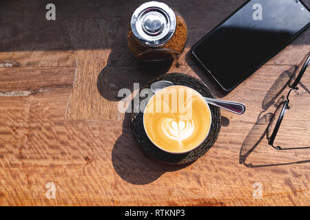 Vue de dessus de tasse de lait chaud avec du café latte art, smartphone, les lunettes et le sucre brun sur un bureau en bois dans la lumière du matin Banque D'Images