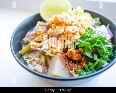 Déchiquetez les nouilles instantanées poulet frit avec de l'ail. le chili en poudre, citron, oignon de printemps et de la soupe avec les épices dans un bol sur le tableau blanc Banque D'Images