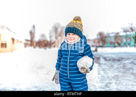 Un petit garçon 3-6 ans pyjama bleu est debout à côté de la grande boule de neige. L'hiver en ville sur fond d'amoncellements de neige et d'arbres. Heureux