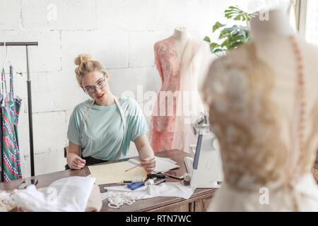 Créateur de mode sur mesure Belle de mesure se situe à dessin en milieu de travail ou de mettre par écrit les résultats après la mesure. Son studio est ensoleillée, pleine de colorf