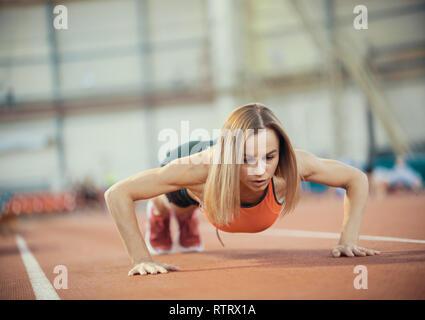 Jeune femme faisant des exercices athlétiques. Faire poussez se lève Banque D'Images
