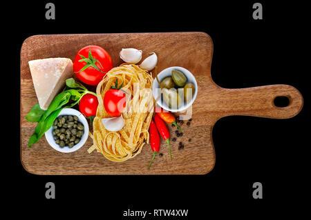 Le parmesan, câpres, Tomates, ail, basilic, piment paprika, poivre et tagliatelles sur planche à découper en bois isolé sur fond noir. Ingrédients