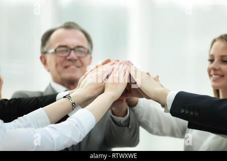 Les gens d'affaires levant les bras lors du meeting in office Banque D'Images