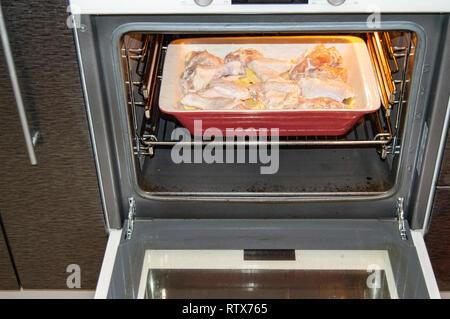 Délicieux avec du poulet rôti et des pommes de terre, crues ingrédients dans une casserole en céramique dans un four chaud pour un dîner en famille Banque D'Images