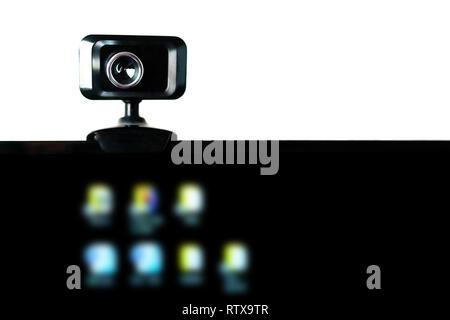USB Webcam, caméra Web, monté sur le moniteur de l'ordinateur avec icônes floue sur écran noir. Streaming vidéo, séminaire, conférence téléphonique. La protection des données, ne Banque D'Images