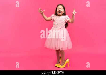 Excité incroyable happy girl in dress dans mama's shoes exprimant à la caméra isolé sur fond rose. Brightful les émotions. Banque D'Images