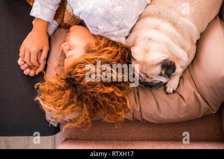 L'amour et de protection et les meilleures amies concept avec belle caucasian woman sleeping près de son joli petit chien pug - l'amitié de haut verti Banque D'Images