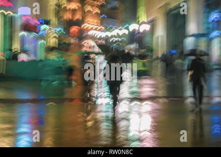 Résumé Contexte des personnes floue sous parasols qui se précipitait en bas la rue de ville en soir de pluie, l'impressionnisme style, éclairage coloré, motion Banque D'Images