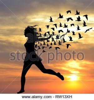 Silhouette de jeune femme sautant avec les oiseaux provenant de son Banque D'Images