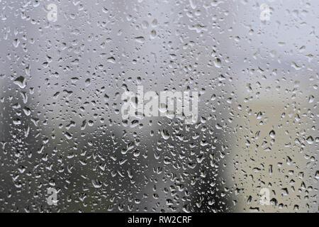 Gouttes de pluie sur les vitres à l'arrière-plan flou jour de pluie à l'extérieur bleu ciel nuage - Image de texture Banque D'Images