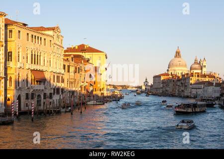 Coucher du soleil doré sur le Grand Canal et Basilica di Santa Maria della Salute, Venise, Vénétie, Italie avec le trafic de bateaux et des réflexions sur l'eau