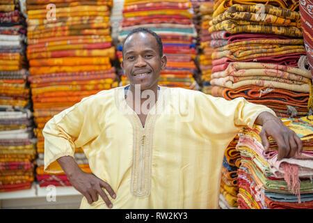 Homme marocain en face de tapis tissé coloré à Ouarzazate, Atlas, Maroc