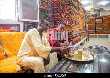 Deux hommes boire le thé ensemble dans une boutique de tapis de luxe, Ouarzazate, Atlas, Maroc