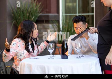 Couple sur une date en colère contre une serveuse dans un restaurant en plein air. Ils sont mécontents et insatisfaits de la service à la clientèle ou la nourriture dans le café. E Banque D'Images