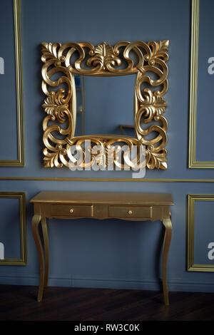 Un miroir et une table de couleur or. Sur l'arrière-plan de la Murs gris classique.l'intérieur du Palais Banque D'Images
