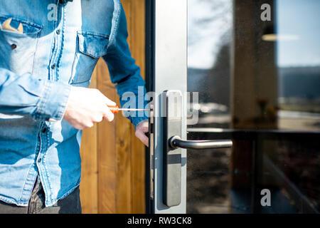La réparation de l'homme de l'entrée de serrure de porte porte en verre, close-up view avec pas de visage Banque D'Images