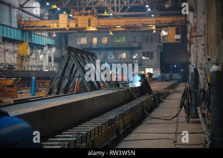 Un homme à l'aide d'une machine de soudage travailleur sur un chantier de construction à l'intérieur Banque D'Images