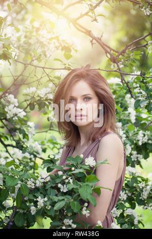 La beauté naturelle. Beau modèle féminin girl au printemps blossom park. Jeune femme parfaite sur fond de fleurs de printemps Banque D'Images