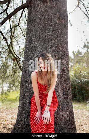 Jeune femme souriante avec robe rouge se penchant vers l'appareil photo Banque D'Images