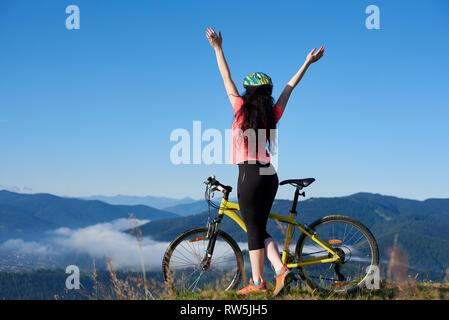 Vue arrière de femme sportive biker debout avec ses mains avec yellow bicycle sur le sommet de la montagne, le port de casque, profitant de matin de brume dans la vallée. L'activité de plein air, style de concept. Copy space Banque D'Images