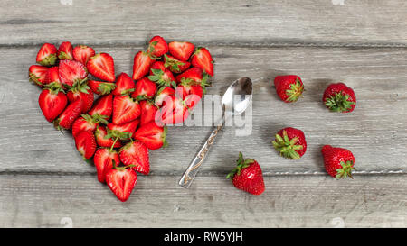 Vue d'en haut, morceaux de fraises disposées en forme de cœur, une cuillère et quelques fraises renversé près, sur bois gris 24. Banque D'Images