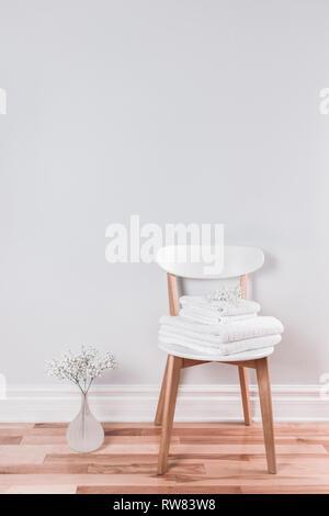Serviettes de ratine blanche sur une chaise dans un intérieur lumineux décoré de gypsophile fleurs. Banque D'Images