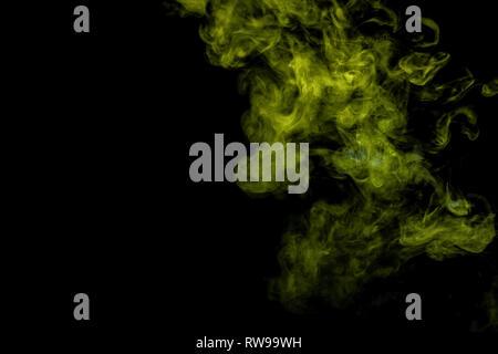 L'art abstrait de couleur bleu et vert sur fond noir de fumée isolés. Arrêter le mouvement de la fumée multicolore sur fond sombre