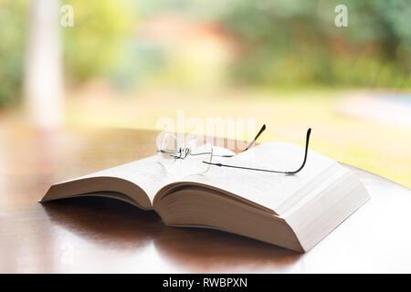 Lunettes de lecture sur le dessus d'un livre Banque D'Images