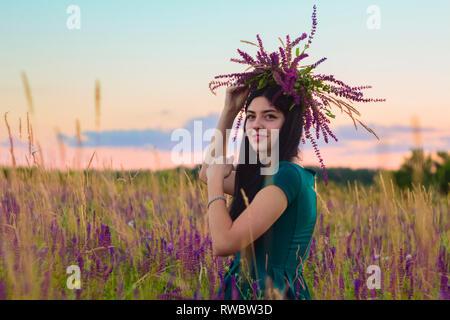Beautiful happy brunette girl avec couronne dans les mains assis dans le champ de fleurs sur fond de paysage au coucher du soleil l'été en Ukraine.