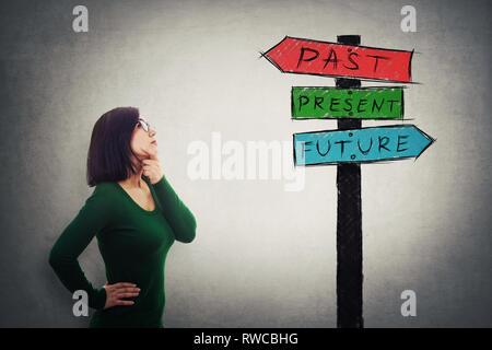 Pensive young businesswoman looking up at un panneau avec des flèches indiquant le passé, le présent et les orientations futures. Perdu dans le temps pittoresque route signe, dest Banque D'Images