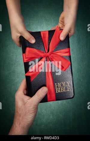 Main de l'homme de donner à un enfant une Sainte Bible comme un cadeau, attachés en ruban rouge