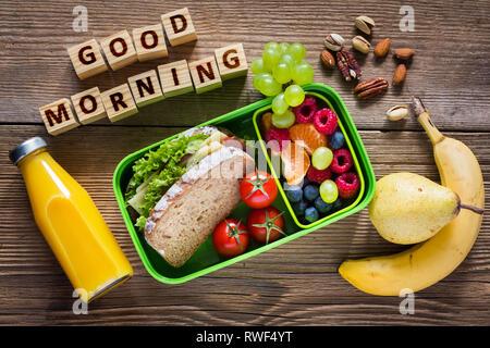 De saines habitudes alimentaires concept. Déjeuner à l'école fort avec sandwich, fruits, légumes, jus d'orange et les noix. Banque D'Images