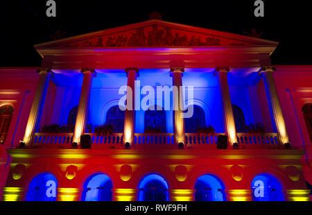 Le théâtre Sucre illuminé par le rouge, le jaune et le bleu dans le centre historique de la ville de Quito, Equateur. Banque D'Images