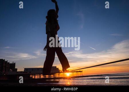Météo France: février le plus chaud jamais enregistré au Royaume-Uni à Ceredigion.Ici femme,femme,university étudiant sur une slack line, slackline, Aberystwyth, Pays de Galles,plage,UK, Banque D'Images