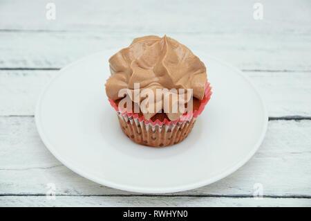 Biscuit gâteau avec crème au chocolat sur une plaque blanche sur un fond de bois blanc. Banque D'Images