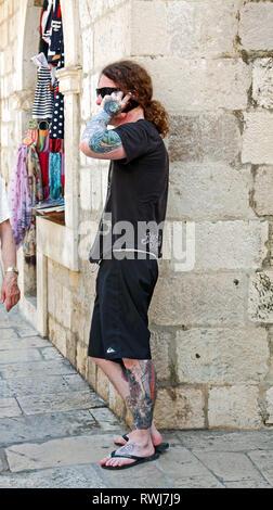 Fortement tattooed man, talking on cell phone; cheveux longs; queue de cheval, des vêtements noirs; décorations de la peau, de la vieille ville de Dubrovnik, Croatie; Europe; été; vert Banque D'Images