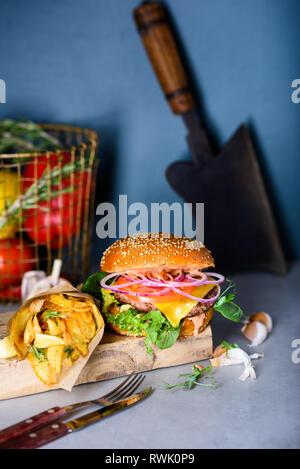 Burger de boeuf grillé avec de la laitue et de la mayonnaise frites servi sur une table ou un comptoir, avec copyspace Banque D'Images