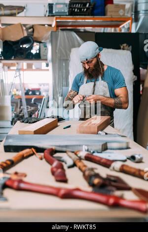Ax travaillant sur le bois pour manche de hache en atelier