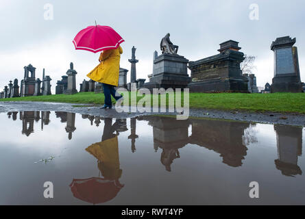 Femme en robe jaune et parapluie rouge reflète dans flaque autour de cimetière nécropole à Glasgow, Écosse, Royaume-Uni