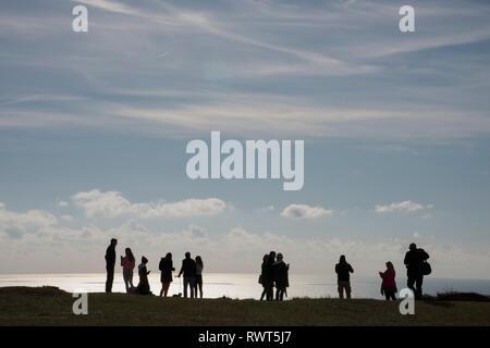 Groupe mixte de personnes en silhouette debout sur le bord de Beachy Head sur le South Downs Way Angleterre Royaume-uni. Banque D'Images